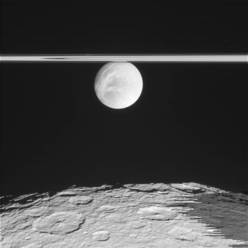Поверхность Реи. Выше перед нами находится еще однин спутник Сатурна - Диона на фоне колец Сатурна.
