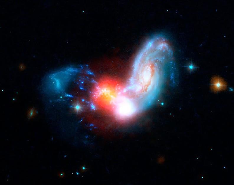 Взаимодействующие галактики II Zw 096. Яркое пятно в центре - область активного звездообразования. Фото NASA/JPL-Caltech/STScI