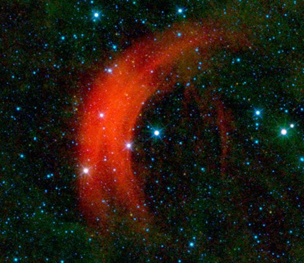В центре изображения звезда Альфа Жирафа, красная дуга слева от нее – результат взаимодействия звездного ветра с «фоновым» веществом. Фото NASA / JPL-Caltech / WISE Team