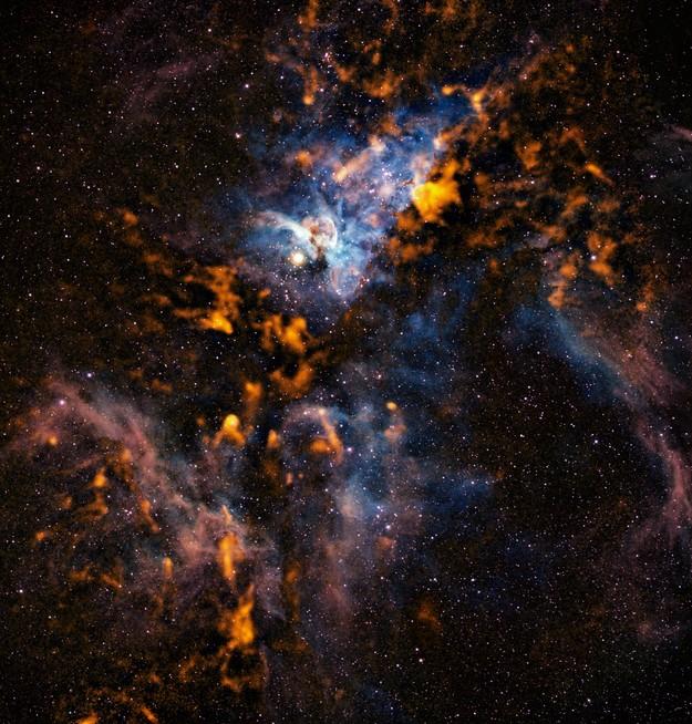 Изображение показывает наблюдения радиотелескопа APEX (оранжевые тона), объеденное с наблюдениями в видимом диапазоне. Фото ESO/APEX/T. Preibisch et al. (Submillimetre); N. Smith, University of Minnesota/NOAO/AURA/NSF (Optical)