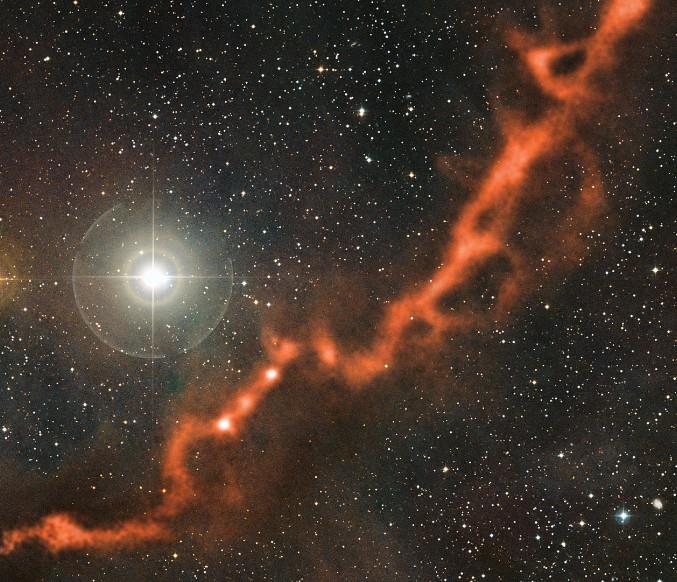 Нитевидное скопление пыли и газа в Тельце. Данные с телескопа APEX (оранжевый цвет) были наложены на обычную оптическую фотографию звездного неба. Фото ESO/APEX (MPIfR/ESO/OSO)/A. Hacar et al./Digitized Sky Survey 2. Acknowledgment: Davide De Martin