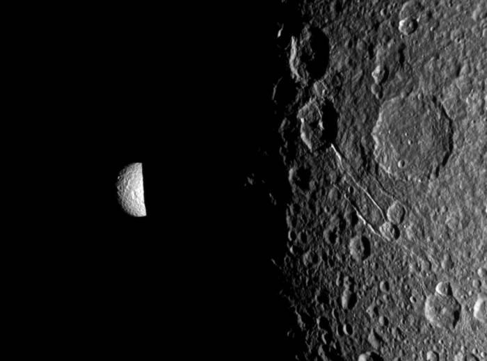 Мимас выглядывает из-за ночной стороны Дионы. Фото NASA/JPL-Caltech/Space Science Institute