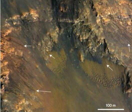 Фотография показывает темные полосы в огромном каньоне, который является частью системы Долина Маринера.