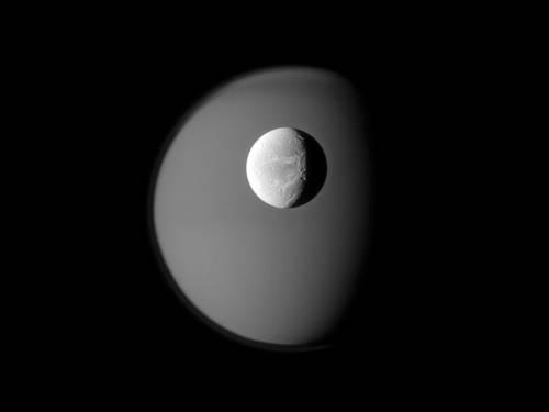 Диона на фоне Титана.